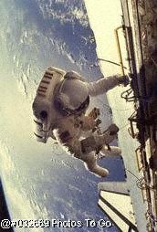 astronaut floating next to craft