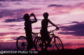 Silhouette of mountain bikers at sunset